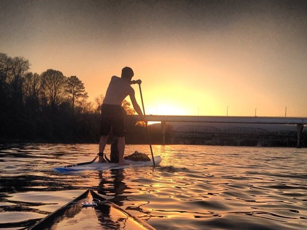 Andrew Bryne paddling around the island at sunset. Photo by Jake Wheeler