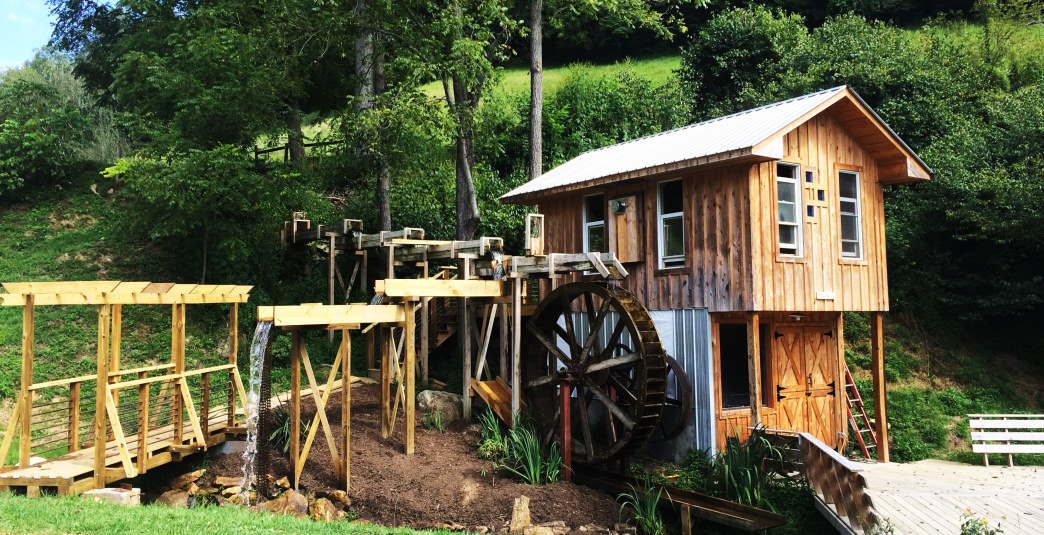 The Mill House is a small and creative two-story cabin complete with a working waterwheel.