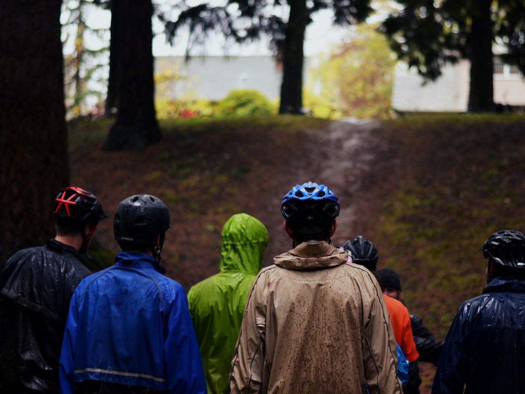 A group of riders gearing up for a muddy ride on a wet Portland trail.