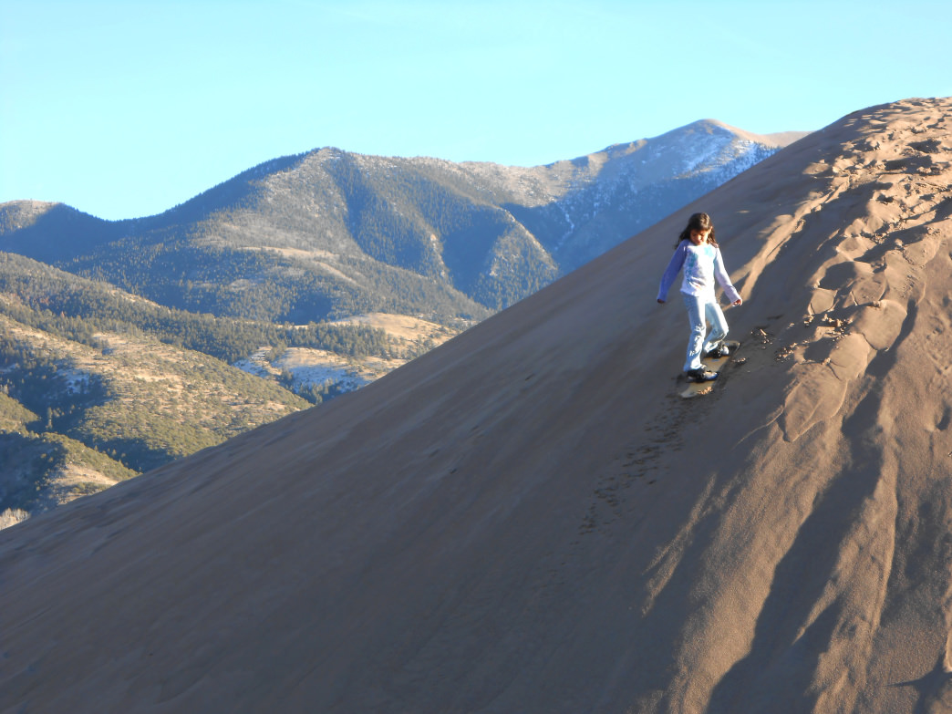 Sandboarding at Great Sand Dunes National Park can be fun for kids and adults.