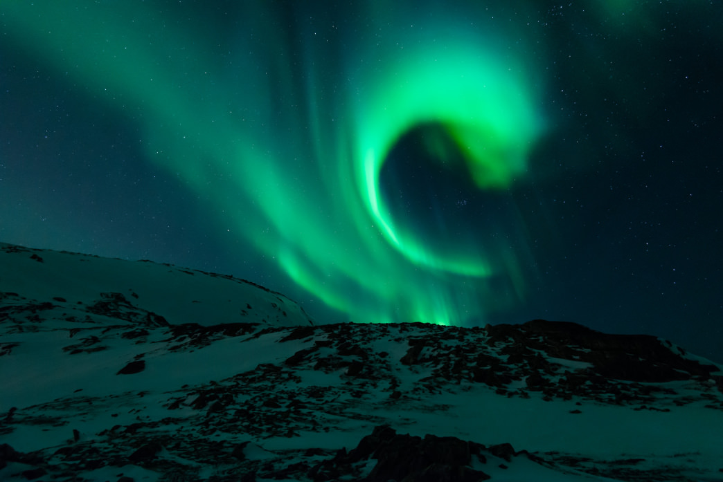 A swirling Aurora above the snow.
