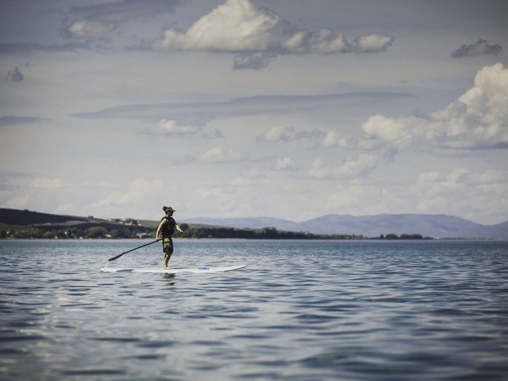 A woman stand up paddle boarding on Bear Lake, Utah