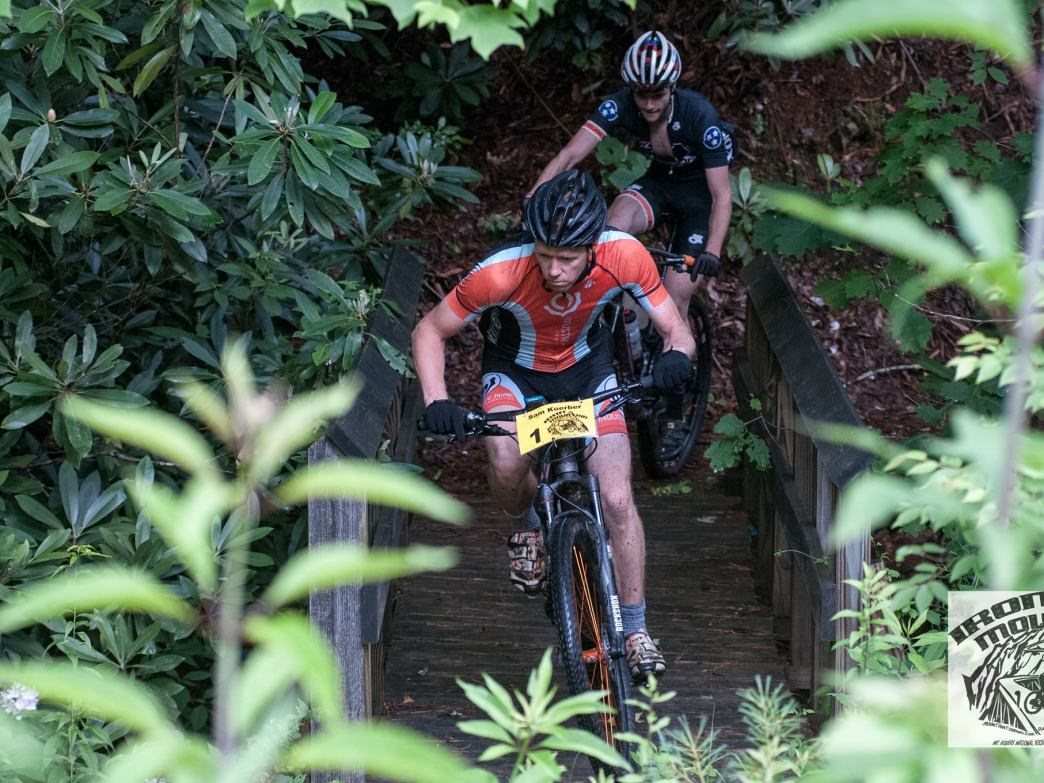 Leaders of the 2015 Iron Mountain 100k cross a bridge deep in the forest.