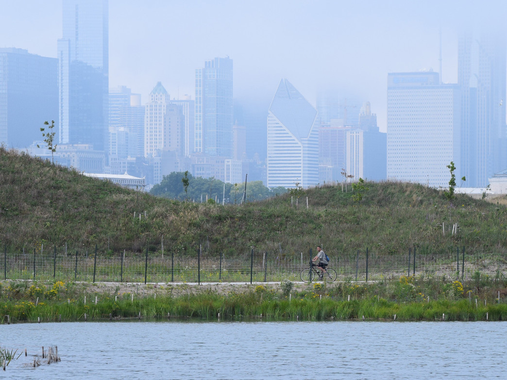 A cyclists rides the concrete path on Northerly Island with a hazy view of Chicago behind him.