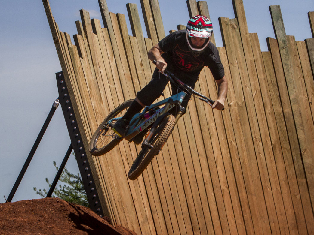 A mountain biker launches off the wall ride on the Devil's Racetrack at Baker Creek Preserve in Knoxville. .