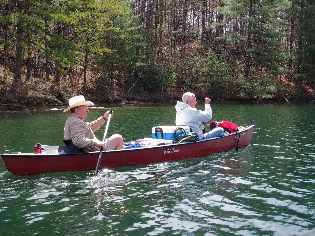 Two men paddle their canoe close to the shore of Lake Jocassee.