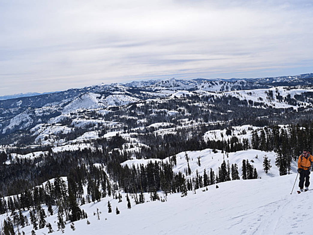"""Skinning up for another lap on Castle Peak with great views with the I-80 corridor below and the Lake Tahoe Basin visible on the left. You can even see the avalanche scar from the """"Elevens"""" on Trimmer Peak in South Lake on the left and the peaks of the Sierra Crest stretching southward."""