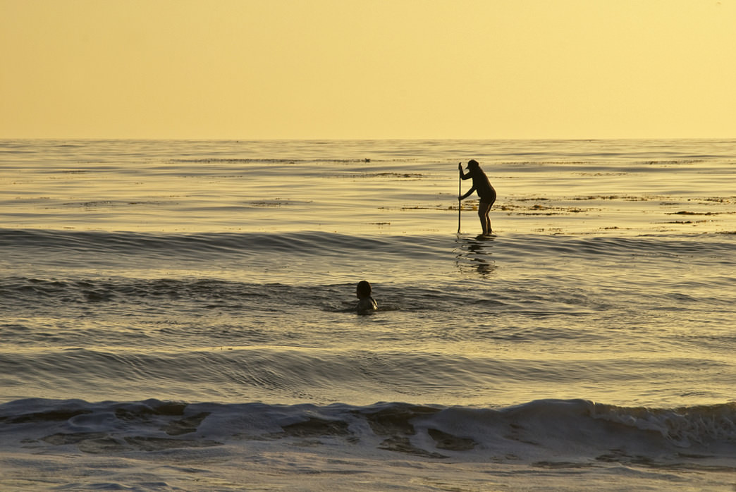 A paddle surfer searching for the last waves of the day