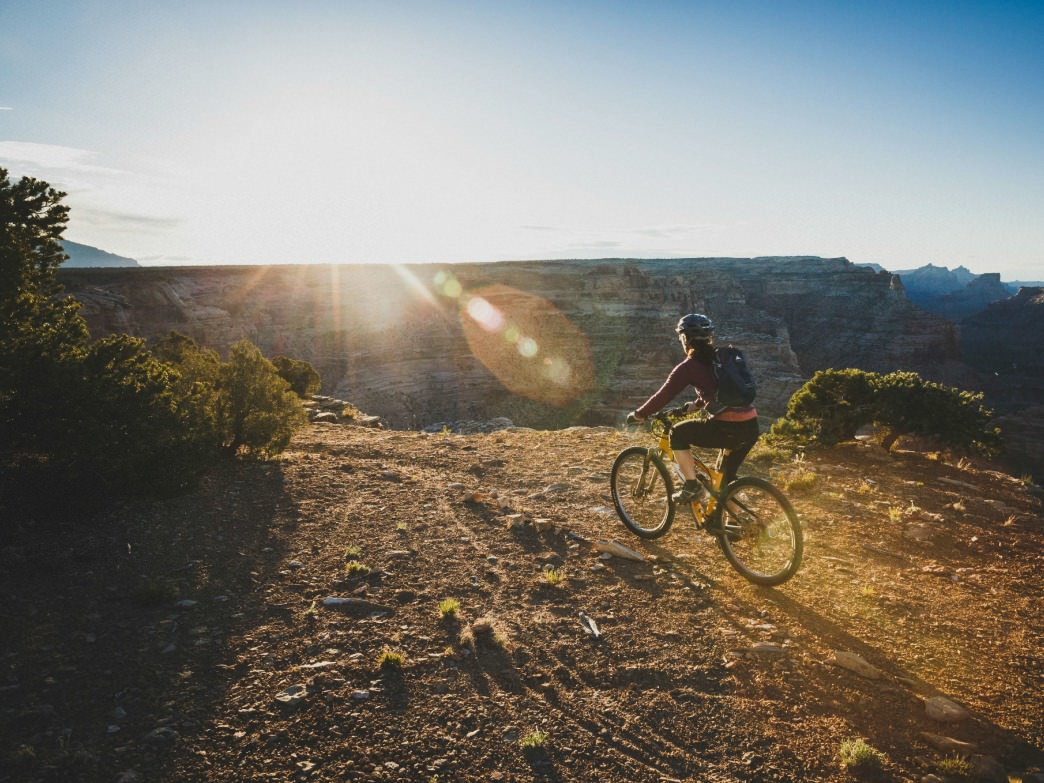 A woman rides the Good Water Trail at sunrise, the Wedge, San Rafael Swell, Utah