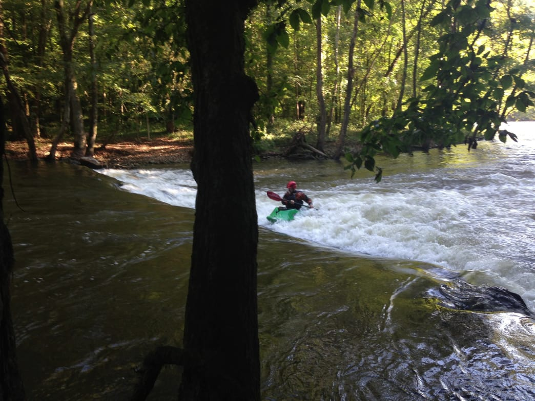 Erich Burton surfs the play hole on the Pigeon River.