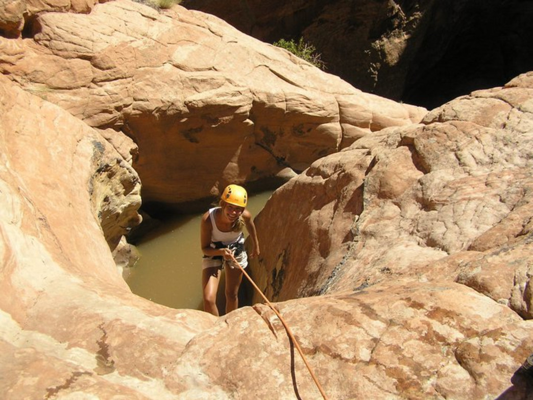 The author rappelling onto the rim of a pothole near Escalante, Utah.