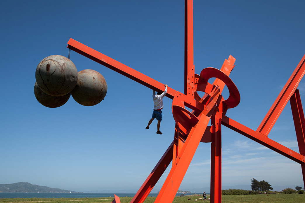 Alex Honnold dangles from an urban art sculpture in San Francisco.